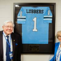Don and Nancy Lubbers posing in front of a framed Lubbers jersey in the Jamie Hosford Football Center.